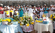 Candomble group in traditional white dress taking part in a public ceremony on the beach. Offerings and flowers on a table in the foreground. February 2nd is the feast of Yemanja, a Candomble Umbanda religious celebration, where thousands of adherants visit the Rio Vermehlo Red River to make offerings of flowers and prayers, paying their respects to Yemanja, the Orixa goddess of the Sea and water.