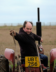 © Licensed to London News Pictures. <br /> 30/11/2014. <br /> <br /> Boulby, United Kingdom<br /> <br /> Ian Myers from York makes adjustments to his plough as he drives a 1958 McCormick International tractor as he takes part in a ploughing match that takes place each year on fields next to the picturesque Yorkshire coastline near Staithes. Farmers attend each year to demonstrate their ploughing skills and to help raise money for charity with proceeds from this year going to Charlie Brown Cancer Care in Newcastle.<br /> <br /> <br /> Photo credit : Ian Forsyth/LNP