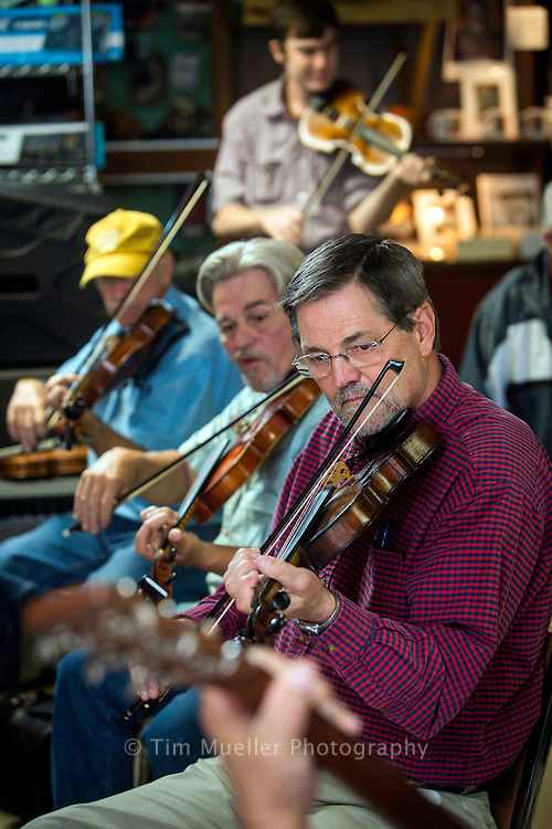 From the bottom right, Scott Romero, Tim Monte and Gene Segura perform at the Savoy Music Center. The music store in Eunice, La. hosts an acoustic jam session every Saturday morning where local musicians gather to play. in the background is Jim Marcantel.