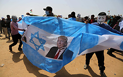 April 13, 2018 - Khan Younis, Gaza Strip, Palestinian Territory - Palestinians prepare to set fire on an Israeli flag and portraits of US President Donald Trump and Saudi Crown Prince Mohammed bin Salman during a tent city protest where Palestinians demand the right to return to their homeland, at the Israel-Gaza border, in Khan Younis in the southern Gaza Strip.   (Credit Image: © Ashraf Amra/APA Images via ZUMA Wire)