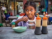 11 SEPTEMBER 2013 - BANGKOK, THAILAND:  A girl in her school uniform eats Mama Noodles, the Thai version of Japanese instant Ramen noodles, at a street side food stall in the Chinatown section of Bangkok. Thailand in general, and Bangkok in particular, has a vibrant tradition of street food and eating on the run. In recent years, Bangkok's street food has become something of an international landmark and is being written about in glossy travel magazines and in the pages of the New York Times.        PHOTO BY JACK KURTZ