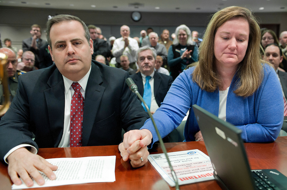 Mark and Cindy Mattioli hold hands as they receive a standing ovation after testifying at the Legislative Office Building in Hartford, Conn., Monday, Jan. 28, 2013. Mark Mattioli whose 6-year-old son James Mattioli was killed at Sandy Hook, said there are more than enough gun laws on the books, but they are not being properly enforced. (AP Photo/Jessica Hill)
