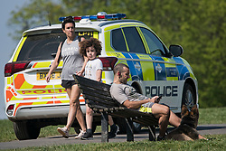 © Licensed to London News Pictures. 10/04/2020. London, UK. A Police patrol car drives past a man sitting down on Primrose Hill in London, during a pandemic outbreak of the Coronavirus COVID-19 disease. The public have been told they can only leave their homes when absolutely essential, in an attempt to fight the spread of coronavirus COVID-19 disease. Photo credit: Ben Cawthra/LNP