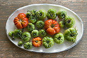 Striking red and green colours of home grown British tomatoes freshly plucked from a vine and placed on a china platter on a rustic table in England