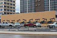 Mural with a row of pump jacks on a building in downtown Midland, Texas.Midland is the headquarters for oil production activity  in the Permian Basin.   The Basin is in the north western part of Texas and the southeastern part of New Mexico.   Oil has been recovered for decades however the fracking industry recently  revived production. Drill sites are all around the cities perimeter, within the city lines.