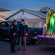 Valeria Mancinas (right) waits on the Feast of Our Lady of Guadalupe float, December 11, 2020, while Father Madhu George (center) and Sgt. Chris Bender (left) discuss the vehicle processions route to Our Lady of the Blessed Sacrament in Miami, Arizona. In non-COVID times, worshippers walk behind the float with candles.