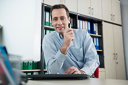 Young man sitting in office working at computer