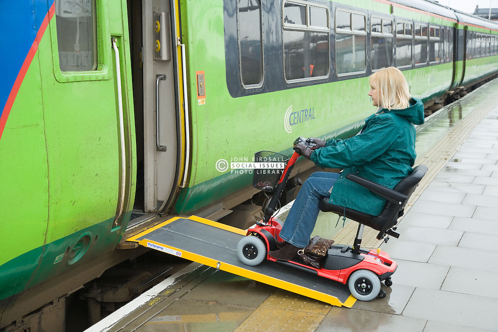 Woman steering electric mobility scooter up access ramp to board a train,