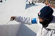A Japanese coach measures the temperature of the snow during the ladies big air qualification of the Pyeongchang Winter Olympics 2018 on February 19th 2018, at the Alpensia Ski Jumping Centre, South Korea