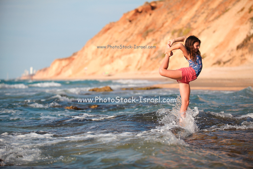 Young girl of 12 does gymnastics on the beach