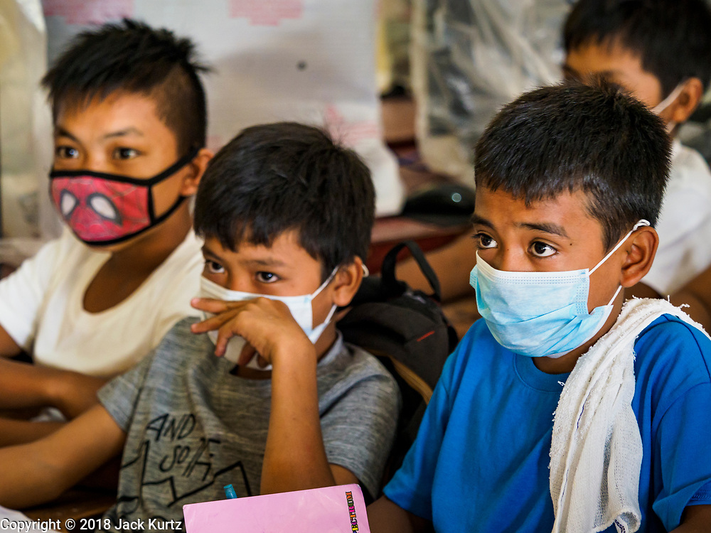 """22 JANUARY 2018 - GUINOBATAN, ALBAY, PHILIPPINES:   Students at Muladbucad Grande Elementary School in Guinobatan wear face masks in a class about volcano preparation. Several communities in Guinobatan were hit ash falls from the eruptions of the Mayon volcano and many people wore face masks to protect themselves from the ash. There were a series of eruptions on the Mayon volcano near Legazpi Monday. The eruptions started Sunday night and continued through the day. At about midday the volcano sent a plume of ash and smoke towering over Camalig, the largest municipality near the volcano. The Philippine Institute of Volcanology and Seismology (PHIVOLCS) extended the six kilometer danger zone to eight kilometers and raised the alert level from three to four. This is the first time the alert level has been at four since 2009. A level four alert means a """"Hazardous Eruption is Imminent"""" and there is """"intense unrest"""" in the volcano. The Mayon volcano is the most active volcano in the Philippines. Sunday and Monday's eruptions caused ash falls in several communities but there were no known injuries.  PHOTO BY JACK KURTZ"""