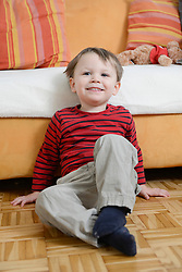 Boy sitting on floor in front of couch, smiling