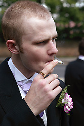 Groom at wedding smoking cigarette,