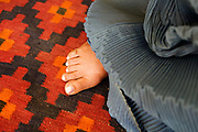 Kabul, Afghanistan. Foot of commercial sex worker Razia, with nail varnish, underneath a burkha.