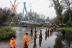 Denham, UK. 8th December, 2020. HS2 security guards form a line across the River Colne in front of Dan Hooper, widely known as Swampy during the 1990s, and a large cherry picker. The climate and roads activist had occupied a bamboo tripod positioned in the river the previous day in order to delay the building of a bridge as part of works for the controversial HS2 high-speed rail link and a large security operation involving officers from at least three police forces, National Eviction Team enforcement agents and HS2 security guards was put in place to facilitate his removal.