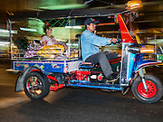 """21 DECEMBER 2015 - BANGKOK, THAILAND: A tuk-tuk, or three wheeled taxi, on the street in front of Pak Khlong Talat, also called the Flower Market. The market has been a Bangkok landmark for more than 50 years and is the largest wholesale flower market in Bangkok. A recent renovation resulted in many stalls being closed to make room for chain restaurants to attract tourists. Now Bangkok city officials are threatening to evict sidewalk vendors who line the outside of the market. Evicting the sidewalk vendors is a part of a citywide effort to """"clean up"""" Bangkok.       PHOTO BY JACK KURTZ"""