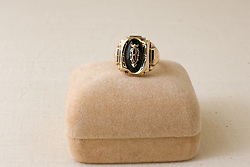 28 January 2011: Studio product shot.  Class ring with emerald, shows use and wear.