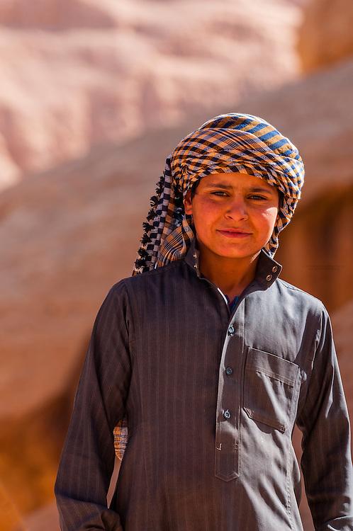 A Bedouin boy at the 100 foot tall Burdah Rock Bridge (an arch), Wadi Rum, in the Arabian Desert, Jordan.