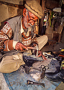 Cobbler at work repairing a boot, Aliabad, Hunza, Pakistan