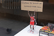 Michael Jordan action figure holding up a sign that you can still shop online as the national coronavirus lockdown three continues on 5th March 2021 in London, United Kingdom. With the roadmap for coming out of the lockdown has been laid out, this nationwide lockdown continues to advise all citizens to follow the message to stay at home, protect the NHS and save lives, and the streets of the capital are quiet and empty of normal numbers of people.