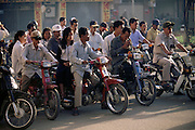 Phnom Penh, Cambodia, Monivong Boulevard early morning rush hour commuters on motorcycles stop at an intersection.