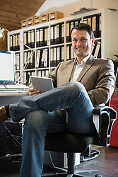 Portrait of a mature businessman using digital tablet in an office, Bavaria, Germany