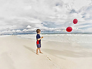 A child plays with balloons on the beach. <br /> © Karen Pulfer Focht-ALL RIGHTS RESERVED-NOT FOR USE WITHOUT WRITTEN PERMISSION