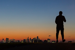 London, October 27 2017. An early morning walker is silhouetted against the dawn light as the day breaks over London's skyline, seen from Primrose Hill. © Paul Davey