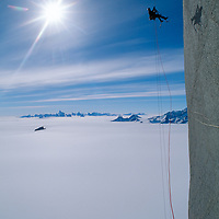 """Conrad Anker ascends a rope high on Rakekniven (""""The Razor""""), a towering granite fin in the Filchner Mountains of Antarctica's Queen Maud Land.  Behind are the Fenris Mountains."""