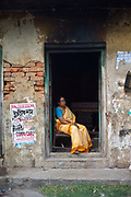 An old woman in the doorway of a house in  Chandannagar, India