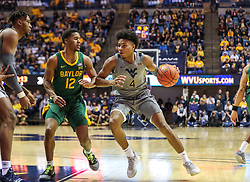 Mar 7, 2020; Morgantown, West Virginia, USA; West Virginia Mountaineers guard Miles McBride (4) drives against Baylor Bears guard Jared Butler (12) during the second half at WVU Coliseum. Mandatory Credit: Ben Queen-USA TODAY Sports