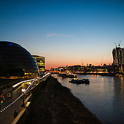 The London city skyline at dusk, as seen from the Tower Bridge. Queen's Walk is at left, with the half-dome of the London City Hall and The Shard standing tall at far left.