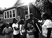 Riverdale Mayor, Deyon Dean (middle) hugs Adonis Bell, 11, after giving Bell and his family a new home while his grandmother, Karen Bell, (right) watches on Tuesday August 25, 2009. Bell helped rescue his family after their Roseland home caught fire last Wednesday morning. Mayor Dean and the village donated the home to Bell and his family.