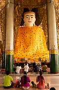 People worshiping a Buddha in one of the temples in the Shwedagon Pagoda Complex, located on Singuttara Hill in the center of Yangon (Rangoon), Myanmar