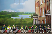 Workmen sit in front of a giant hoarding depicting a classic English country house and it's grounds or gardens, on Bond Street, London, UK. The workers are taking a break from the refurbishment of one of the exclusive shops in the area. The vista creates a weird street scene where rich and poor, wealthy and rich meets the rest of society.