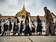 29 OCTOBER 2016 - BANGKOK, THAILAND: A member of the Royal Household watches people waiting in line on the grounds of the Grand Palace in Bangkok to pay homage to the late Bhumibol Adulyadej, the King of Thailand. Saturday was the first day Thais could pay homage to the funeral urn of the late Bhumibol Adulyadej, King of Thailand, at Dusit Maha Prasart Throne Hall in the Grand Palace. The Palace said 10,000 people per day would be issued free tickerts to enter the Throne Hall but by late Saturday morning more than 100,000 people were in line and the palace scrapped plans to require mourners to get the free tickets. Traditionally, Thai Kings lay in state in their urns, but King Bhumibol Adulyadej is breaking with tradition. His urn reportedly contains some of his hair, but the King is in a coffin,  not in the urn. The laying in state will continue until at least January 2017 but may be extended.       PHOTO BY JACK KURTZ