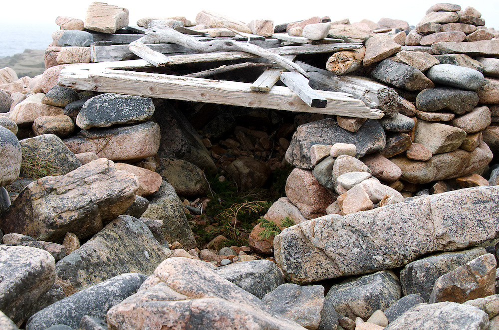 A crude hut built from beach stones and driftwood.