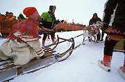 A Sami woman in traditional clothes waits for the officials controlling the Easter reindeer races in Kautokeino, northern Norway, to release the racing bull that will pull her sleigh around the track.
