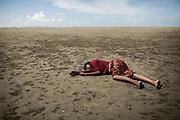 Rohingyas_04<br /> Una mujer yace sin sentido en una playa de Shah Porir Dwip, completamente agotada tras cruzar el río Naf escapando de su persecución en Myanmar. Su familia permanece a su lado en una playa de Shah Porir Dwip. 10/01/2017.
