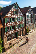 Cyclist passes half-timbered buildings in Schiltach, Kinzigtal Valley, Black Forest, Baden-Wuerttemberg, Germany