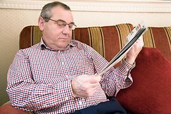 Portrait of an older man reading the newspaper,