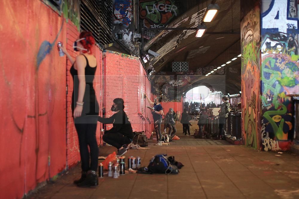 © Licensed to London News Pictures . 08/03/2014. London, UK.  Graffiti writers  join Femme Fierce artists to attempt the Guinness world record to create the largest spray paint mural by multiple artists in Leake Street Tunnel, Waterloo, London. Photo credit: Isabel Infantes /LNP