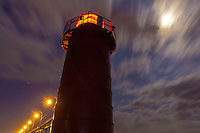 The South haven lighthouse standing against the full moon and streaking clouds