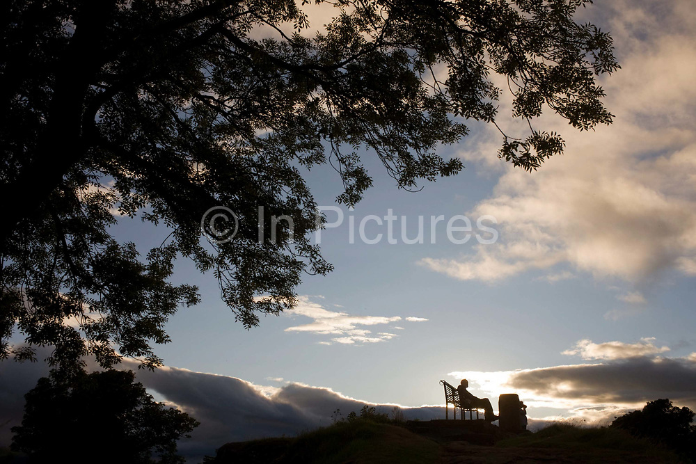 As a summer sun sets behind evening clouds, there is a moment of peace for a solitary man, silhouetted while seated on bench in the cemetery of the Holy Rude Church in Stirling, Scotland. Taking a while to collect his thoughts, to consider aspects of a troubled life or simply to think spiritual meanings, the man has found tranquillity and inner-strength from this beauty spot, a mound overlooking the headstones and graves of Scottish nobility.