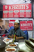 A waiter waits for a serving at the counter at Karims Restaurant, Old Delhi
