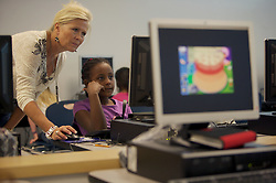 Stock photo of a teacher helping a student in the computer lab at Lovett Elementary School in Houston Texas