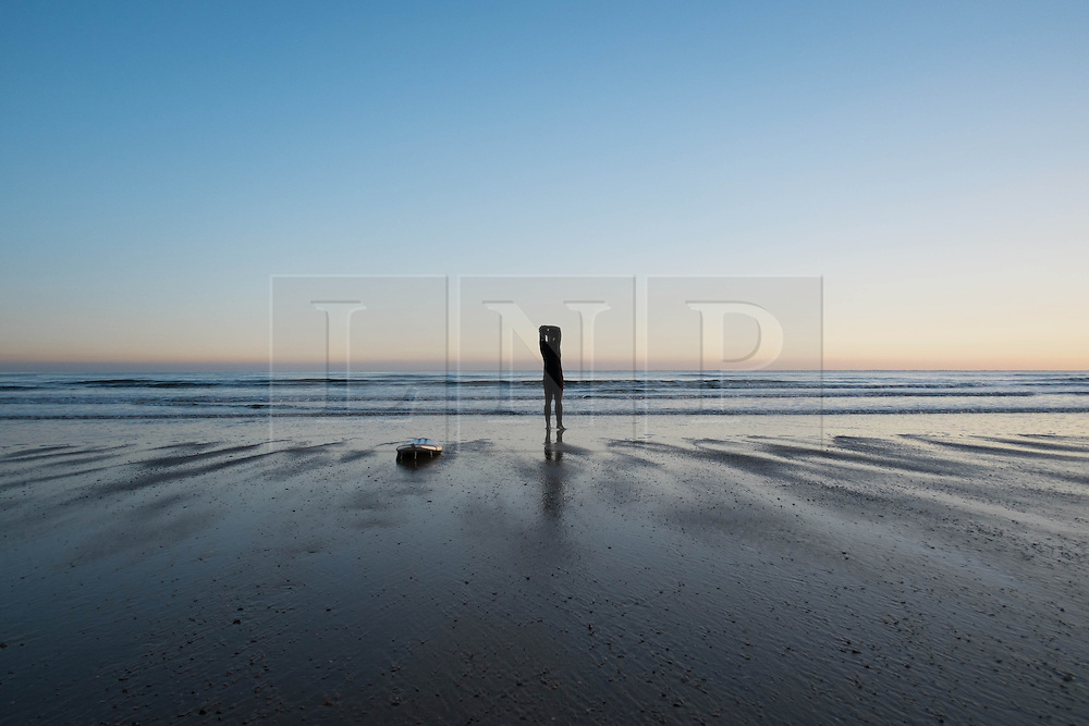 © Licensed to London News Pictures. 12/03/2014<br /> <br /> Saltburn, Cleveland, United Kingdom<br /> <br /> A surfer limbers up before going for an early morning surf as the first light of dawn breaks over Saltburn in Cleveland.<br /> <br /> Photo credit : Ian Forsyth/LNP