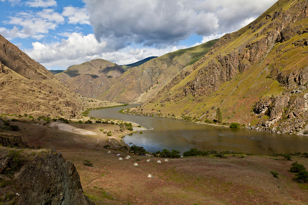 River rafting group camping across from Suicide Jump on the Snake River in Hells Canyon with tents spread out on open meadow.  Licensing and Open Edition Prints