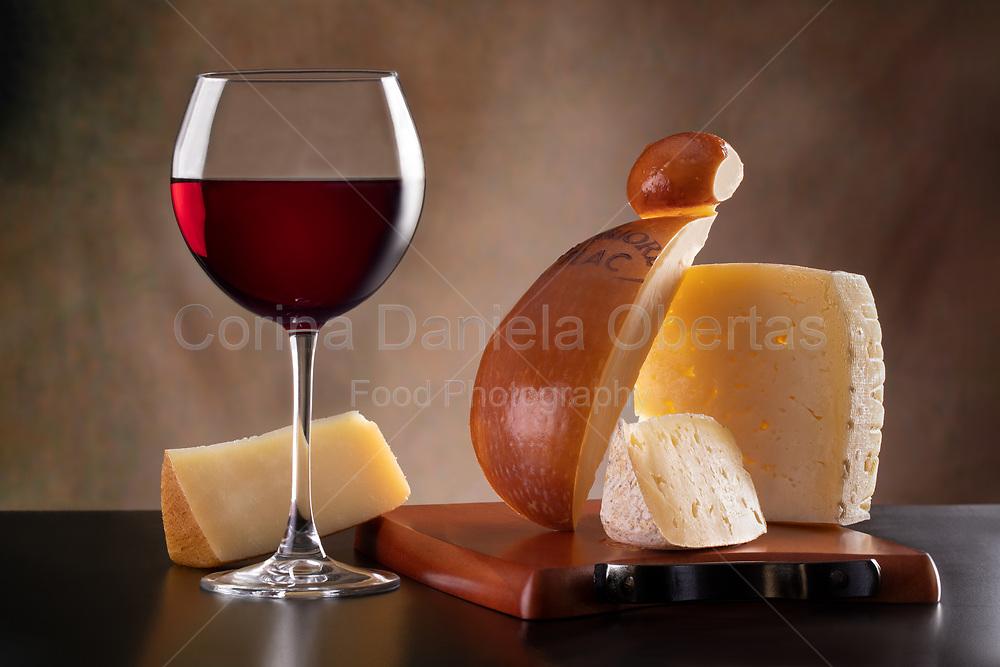 Italian cheese selection and red wine.<br /> Asiago, spicy smoked provolone Valpadana DOP, Sardinian pecorino and Apulian goat cheese Gàlata Casarano.