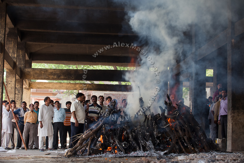Relatives of a deceased person are watching the body being cremated at the traditional 'burning ghat' in Agra. Reduced into ashes it will then be partly thrown into the heavily polluted Yamuna River, flowing next to the Taj Mahal.